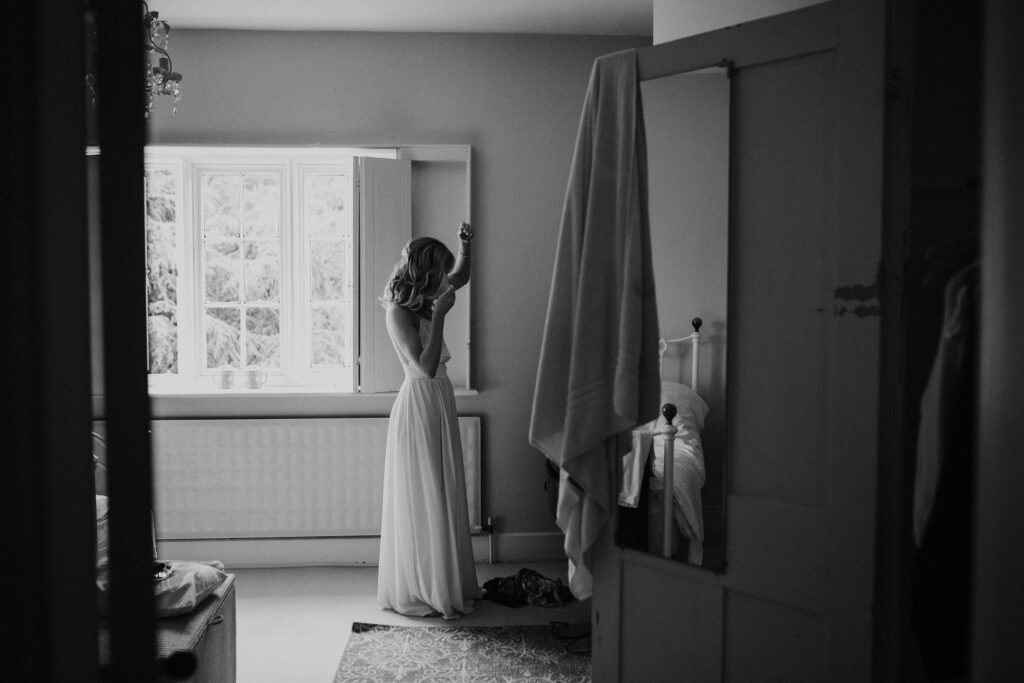 Black and white photo of a bridemaid getting ready in her bedroom in Norfolk.